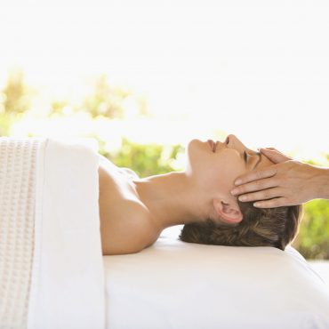Woman receiving facial massage lying on massage table at luxury spa in Napa Valley California