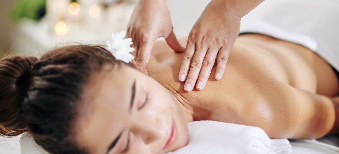 Close-up image of masseuse massaging neck and shoulders of young pretty woman